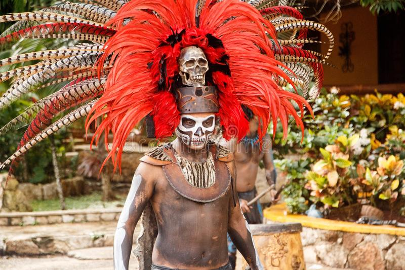 L'uomo si è vestito in un costume azteco variopinto tradizionale con i headress della maschera delle piume nel Messico fotografia stock libera da diritti