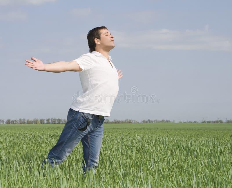 L'uomo si muove in un campo verde di erba immagine stock libera da diritti