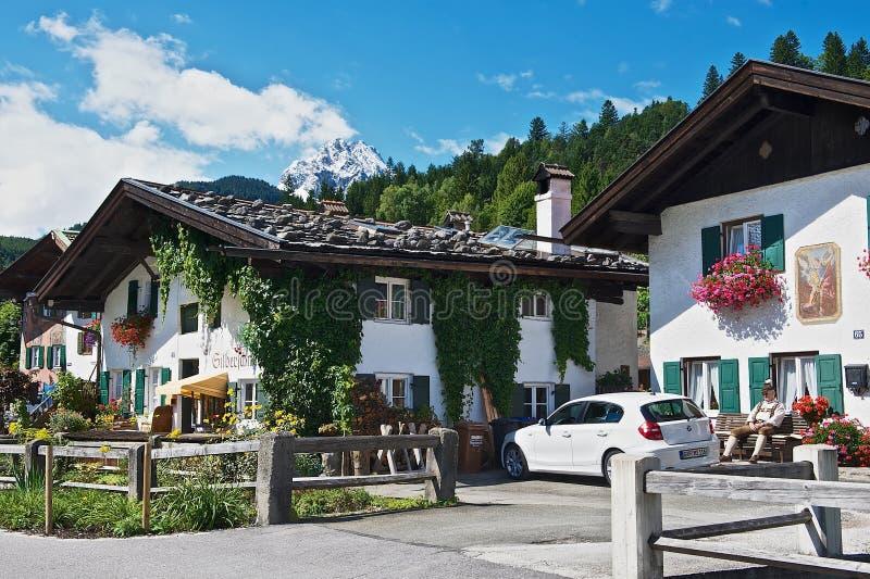 L'uomo si siede davanti alla casa bavarese tradizionale in Mittenwald, Germania fotografia stock