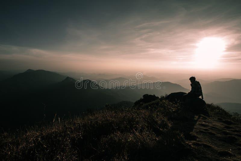 L'uomo si siede sopra una montagna e l'alba godere Viandante stanca r fotografia stock libera da diritti