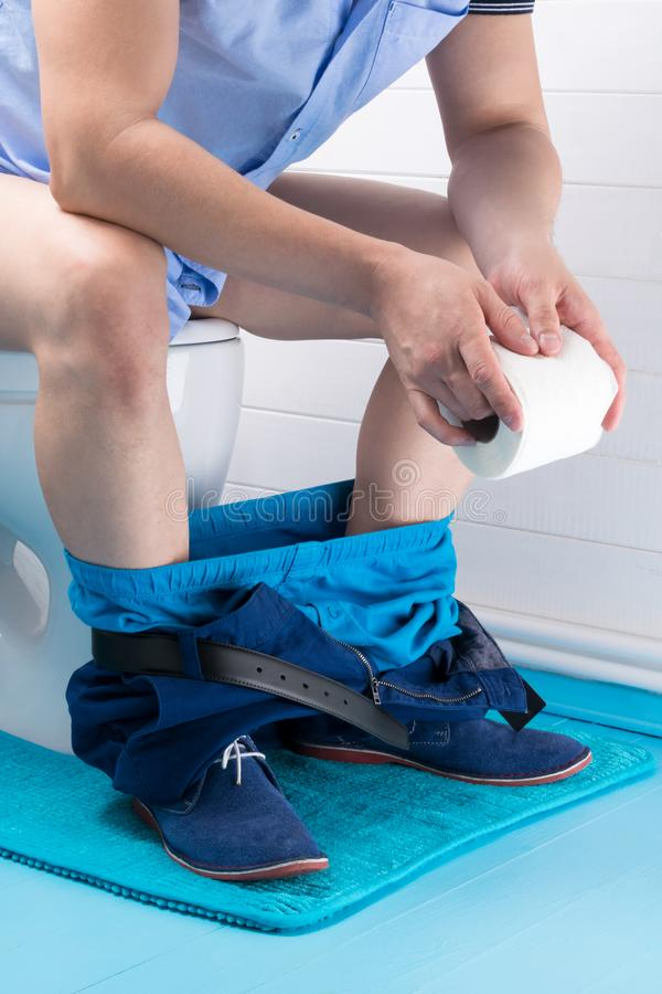 L'uomo si siede su un inserire la toilette e tiene un rotolo di carta in sue mani fotografia stock libera da diritti