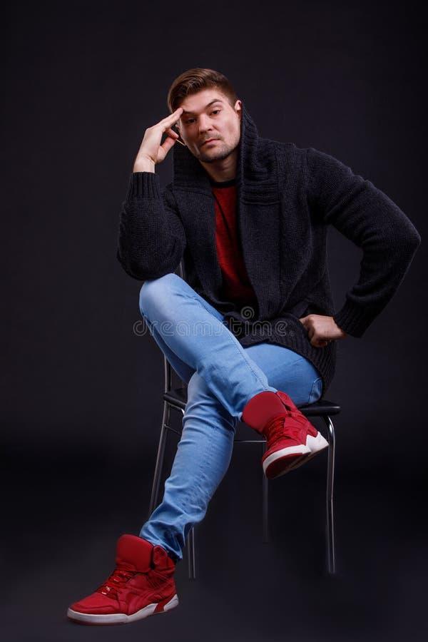 L'uomo si siede su una sedia, tenente una mano vicino alla testa e gli sguardi con uno sguardo pensieroso Su un fondo nero fotografia stock