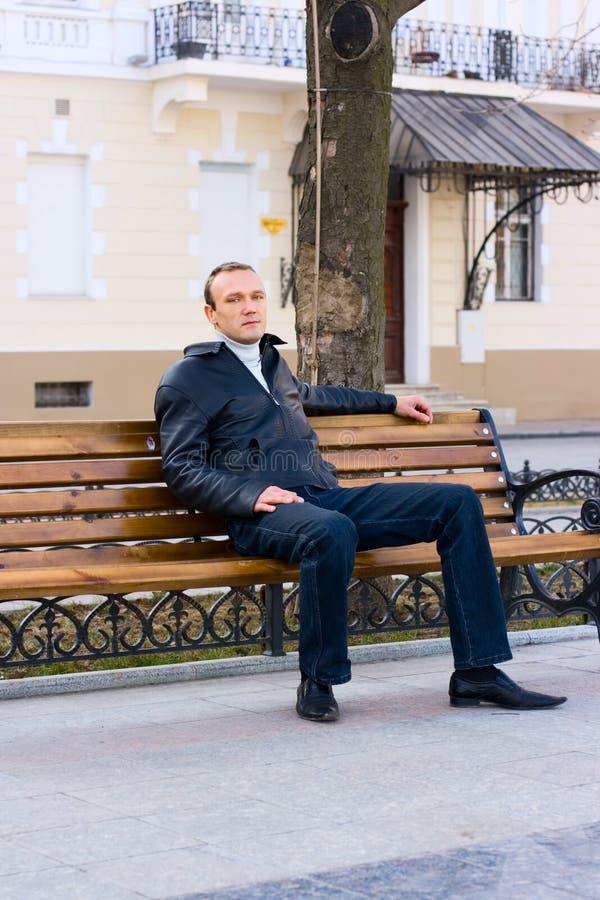 L'uomo si siede sul banco fotografie stock libere da diritti
