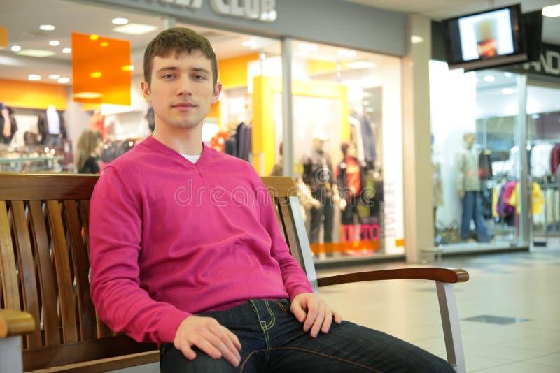 L'uomo si siede sul banco in viale fotografia stock