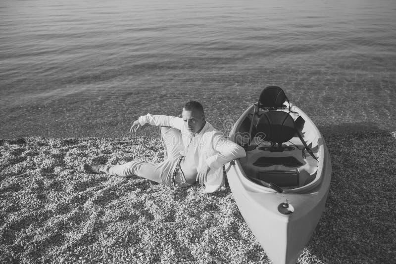 L'uomo si siede sulla spiaggia vicino al crogiolo di canoa il giorno di estate soleggiato, superficie del mare nel fondo Macho co immagini stock