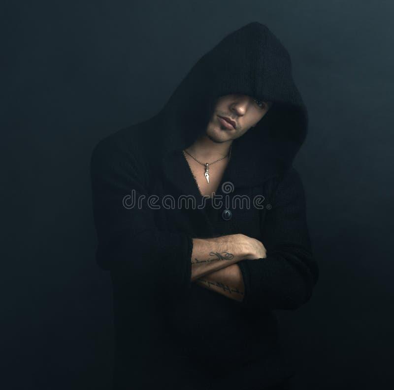 L'uomo sicuro in maglia con cappuccio nera ha attraversato le sue armi immagini stock