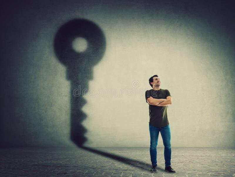L'uomo sicuro, tiene le armi ha attraversato, gettando un'ombra chiave sulla parete Concetto di successo di affari e di ambizione immagini stock