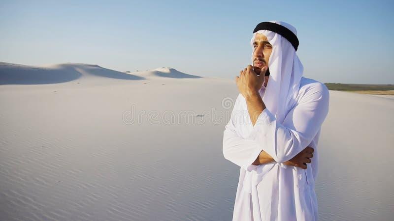 L'uomo signorile di sceicco dei UAE dell'Arabo guarda duro nella distanza e nello stagno fotografia stock libera da diritti