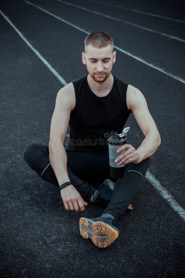 L'uomo snello muscolare nell'addestramento alle bevande dello stadio innaffia da un agitatore di sport sport di ricreazione eserc immagini stock