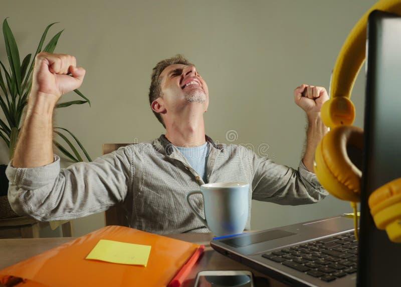 L'uomo soddisfatto e sicuro dei giovani di affari ha eccitato gesturing sulla vittoria come vincitore che lavora a casa l'ufficio fotografie stock libere da diritti