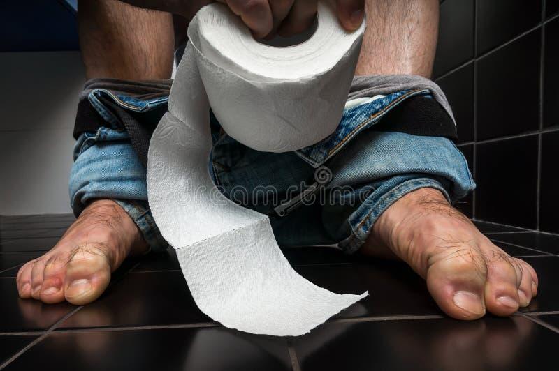 L'uomo soffre da diarrea sta sedendosi sulla ciotola di toilette fotografia stock
