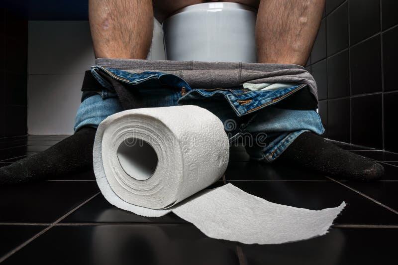 L'uomo soffre da diarrea sta sedendosi sulla ciotola di toilette fotografia stock libera da diritti