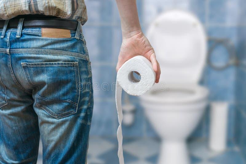 L'uomo soffre da diarrea tiene il rotolo della carta igienica davanti alla ciotola di toilette fotografie stock