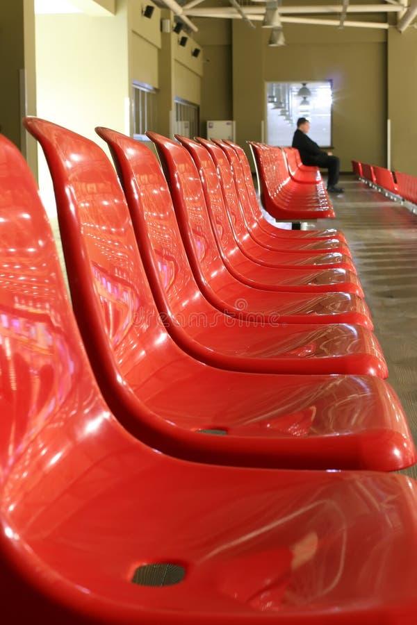 L'uomo solo sta sedendosi sull'ultima sedia nella fila vuota delle sedie rosse fotografia stock libera da diritti