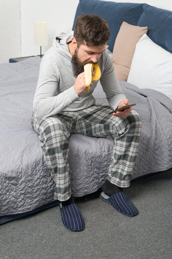 L'uomo sonnolento brutale ha prima colazione in camera da letto maschio maturo con la barba in pigiama sul letto dorma e svegli S fotografie stock libere da diritti