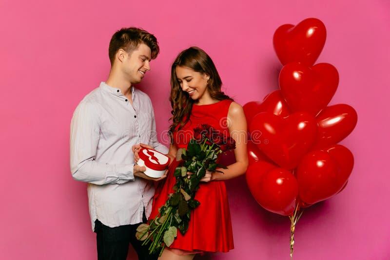 L'uomo sorridente dà le rose rosse e la scatola con il presente alla sua amica affascinante immagine stock libera da diritti