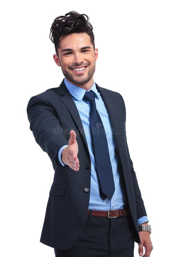 L'uomo sorridente di affari sta accogliendovi favorevolmente con una scossa della mano fotografie stock libere da diritti