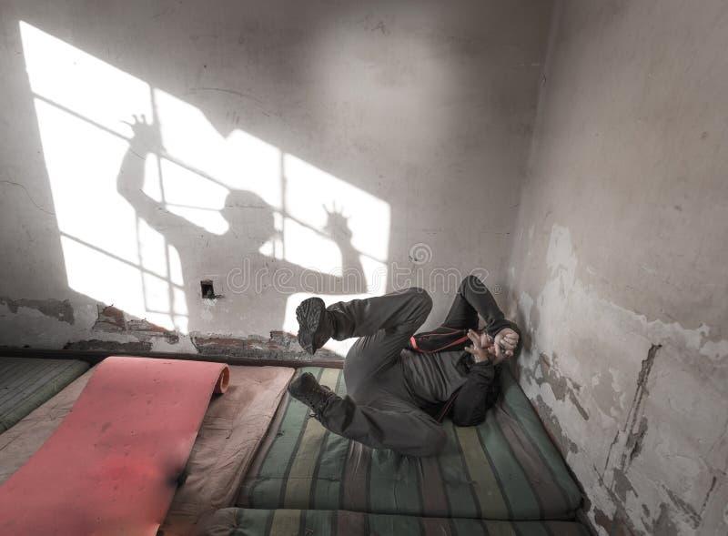 L'uomo spaventato ha terrorizzato il materasso posteriore di menzogne del tipo, la finestra dell'ombra del fantasma, stanza immagini stock libere da diritti