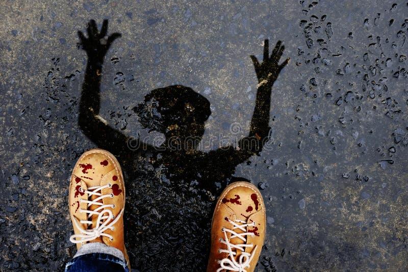 L'uomo spaventoso dello zombie con sangue caduto sulle scarpe alza su Han terrificante fotografie stock