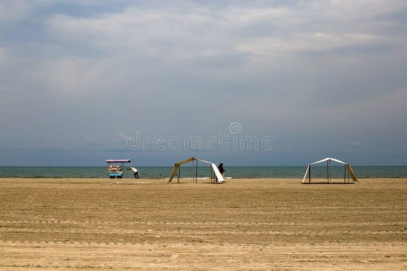 L'uomo spinge il suo carretto dell'alimento su una spiaggia del deserto immagini stock libere da diritti