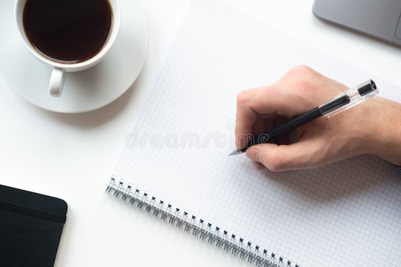 L'uomo sta andando scrivere qualcosa sul taccuino Vista superiore fotografia stock