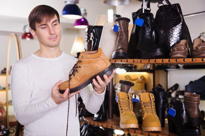 L'uomo sta cercando le scarpe di un winer fotografie stock