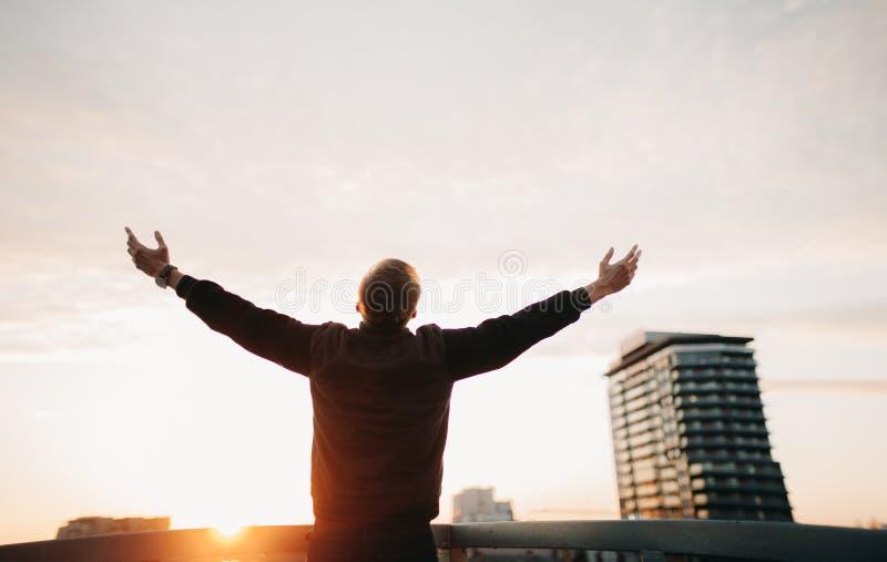 L'uomo sta con la sua parte posteriore sul tetto della casa ed allunga fuori le sue mani su fondo dei grattacieli al tramonto fotografie stock