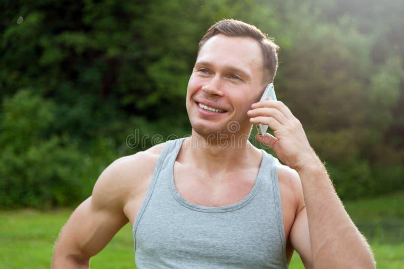 L'uomo sta con un telefono nel parco immagini stock