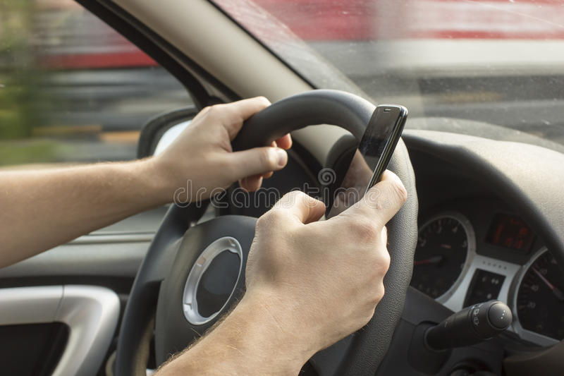 L'uomo sta conducendo un'automobile e sta tenendo un telefono cellulare fotografia stock libera da diritti