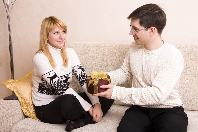L'uomo sta dando la donna dei regali al biglietto di S. Valentino? giorno di s. immagine stock libera da diritti