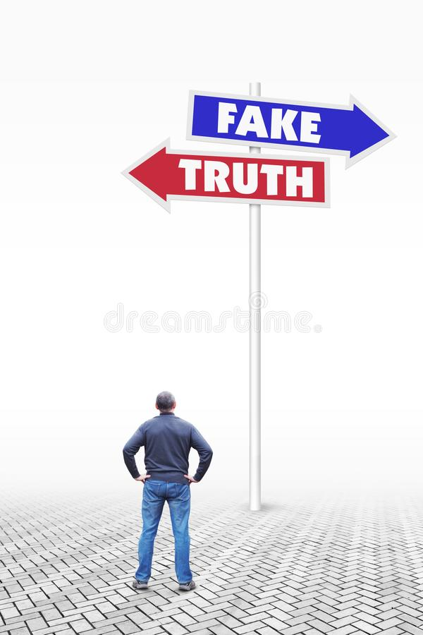 L'uomo sta davanti ad un segnale stradale con le frecce ai lati opposti alla falsificazione ed alla verità immagine stock