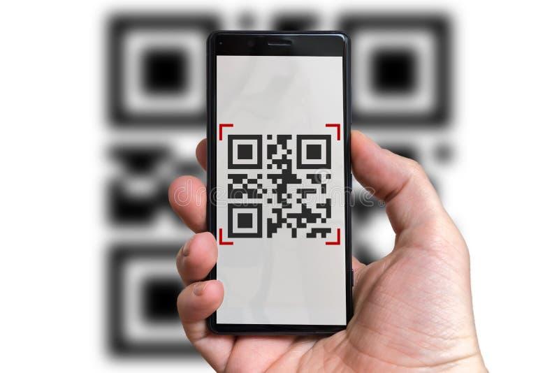 L'uomo sta esplorando il codice di QR con la macchina fotografica in telefono cellulare fotografia stock
