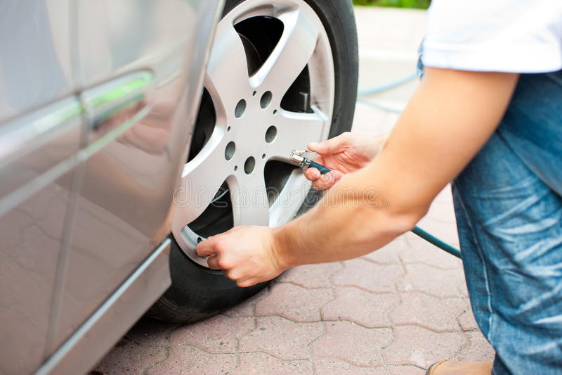 L'uomo sta gestendo la pressione di gomma della sua automobile immagini stock libere da diritti