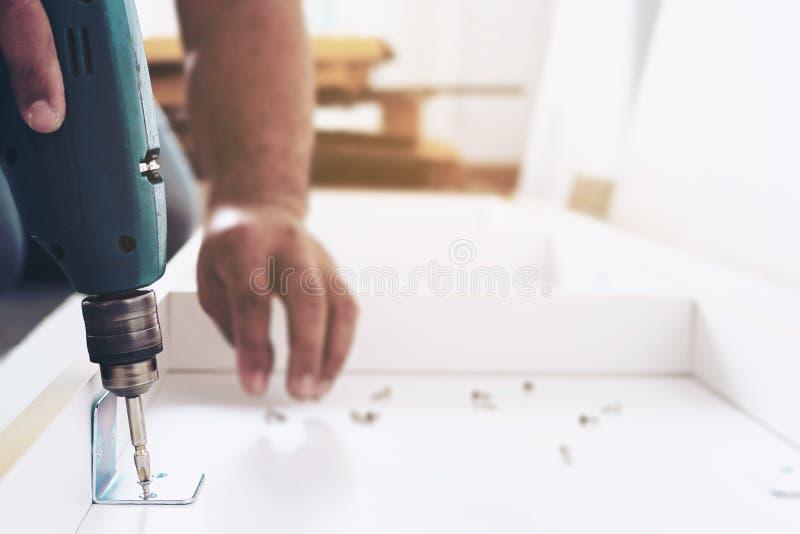 L'uomo sta lavorando con l'assemblea della mobilia utilizzando il cacciavite elettrico nell'installazione della nuova casa immagine stock libera da diritti