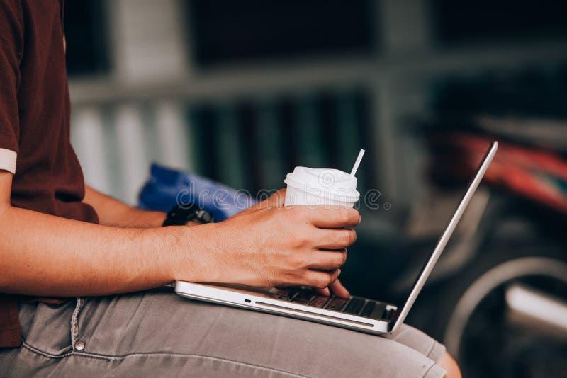 L'uomo sta lavorando usando un computer portatile su tabl di legno d'annata fotografia stock