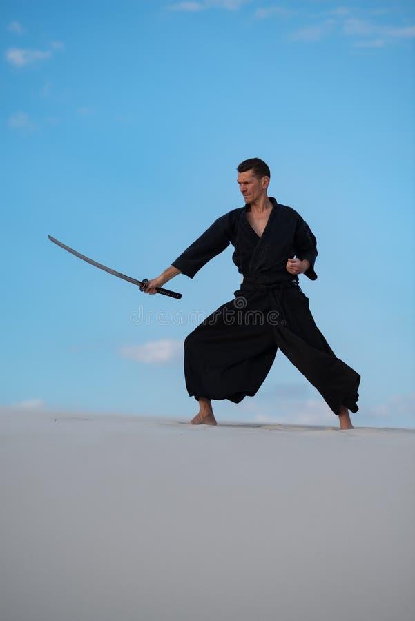 L'uomo sta preparando le arti marziali giapponesi in deserto immagini stock