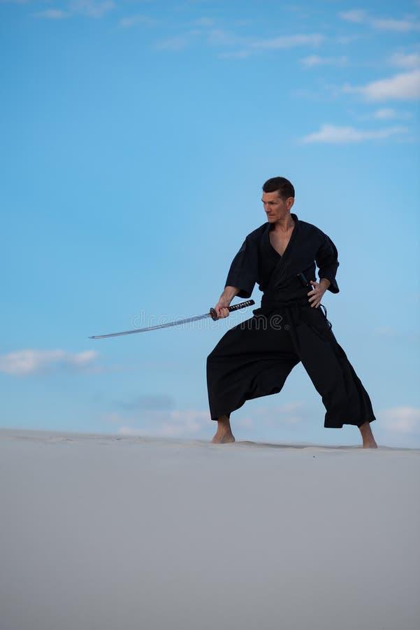 L'uomo sta preparando le arti marziali giapponesi in deserto fotografie stock