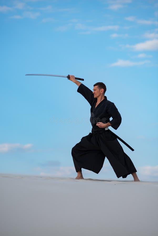 L'uomo sta preparando le arti marziali giapponesi in deserto immagine stock libera da diritti