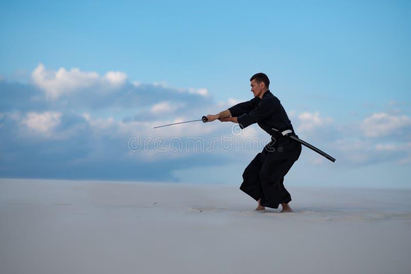 L'uomo sta preparando le arti marziali giapponesi in deserto fotografia stock libera da diritti