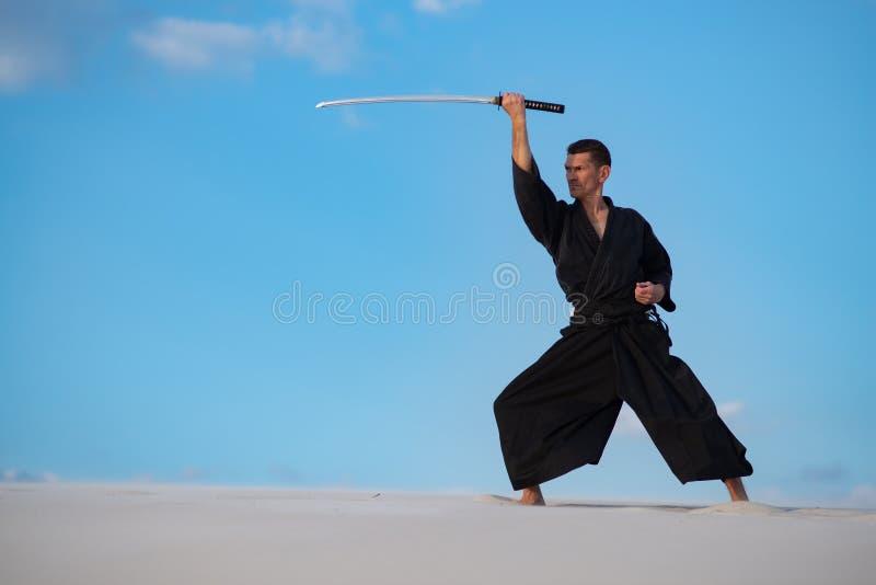 L'uomo sta preparando le arti marziali giapponesi in deserto immagini stock libere da diritti