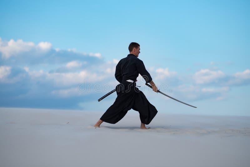 L'uomo sta preparando le arti marziali giapponesi in deserto fotografia stock