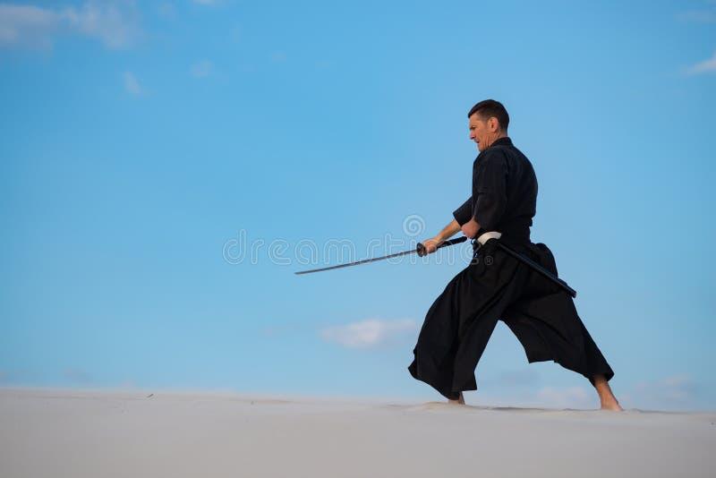 L'uomo sta preparando le arti marziali giapponesi in deserto immagine stock