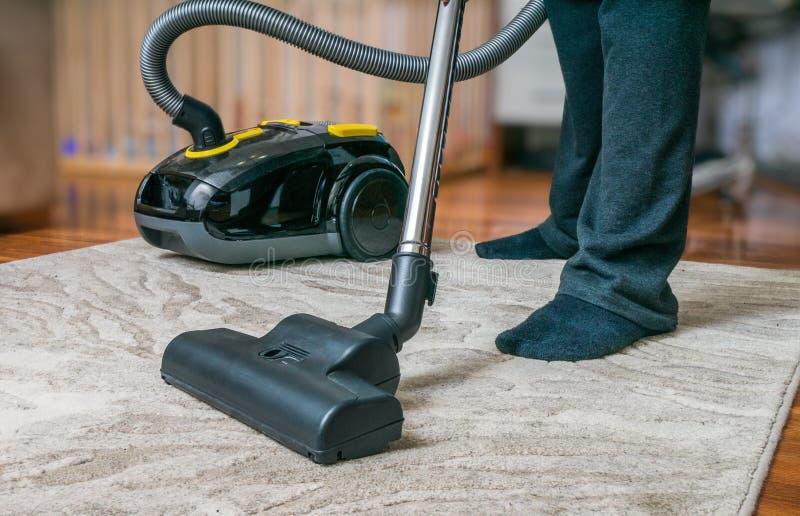 L'uomo sta pulendo il tappeto con l'aspirapolvere fotografia stock libera da diritti