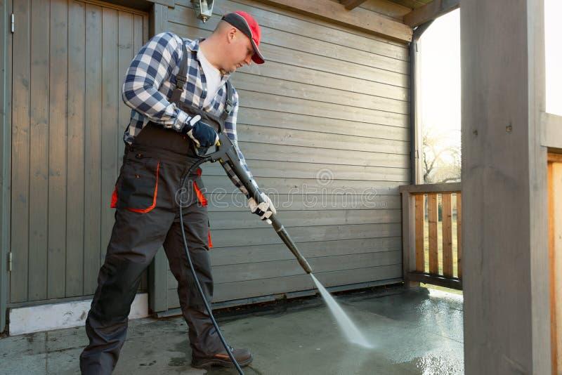 L'uomo sta pulendo il terrazzo con un pulitore ad alta temperatura di pressione sul pavimento di calcestruzzo del terrazzo fotografia stock libera da diritti
