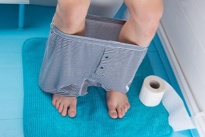 l'uomo sta sedendosi sulla toilette, abbassando i suoi pantaloni ed accanto lui è carta igienica sul pavimento fotografie stock