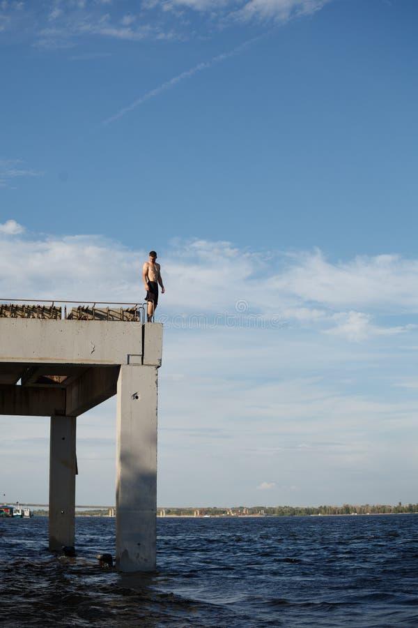 L'uomo sta stando sul pilastro del mare fotografie stock