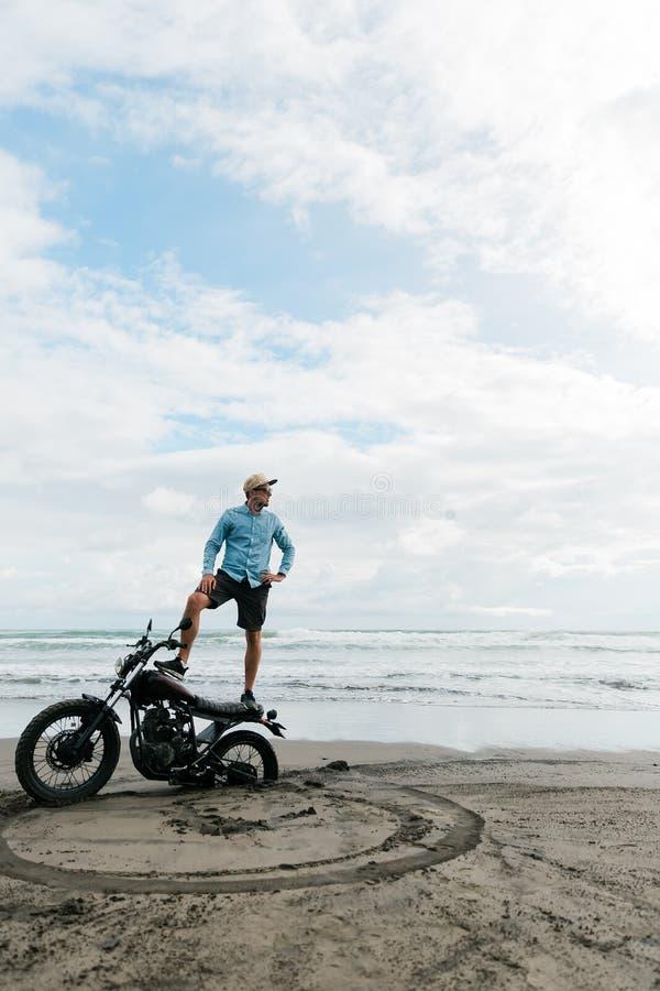 L'uomo sta su un motociclo Spiaggia Bali dell'oceano indietro ruota di un motociclo in sabbia persona di sesso maschile che cerca immagine stock libera da diritti