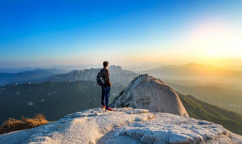 L'uomo sta sul picco della pietra nel parco nazionale di Bukhansan fotografia stock