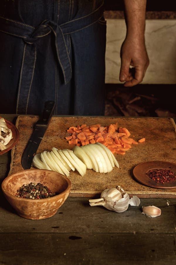 L'uomo sta tagliando le verdure per un piatto Sulla tavola, sull'aglio, sulle cipolle, sulle carote, sui funghi e sulle spezie St immagini stock libere da diritti