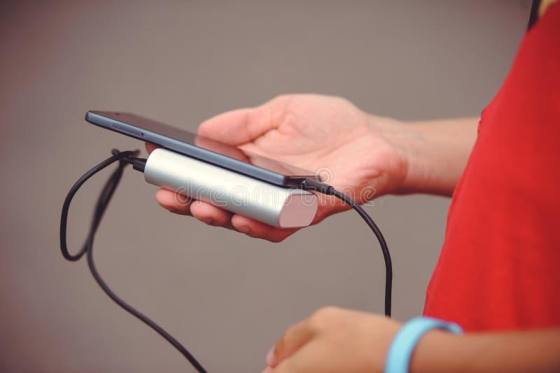 L'uomo sta tenendo il telefono ed il caricatore Powerbank e smartphone disponibili Smartphone della banca di potere del dispositi fotografia stock libera da diritti